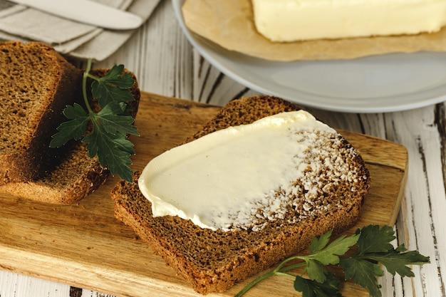 Tranche de pain de seigle beurré sur table en bois