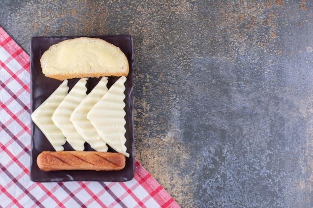 Une tranche de pain servie avec des saucisses et du fromage sur une planche en bois