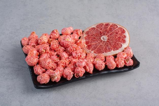 Tranche de pamplemousse à côté d'une portion de bonbons de maïs soufflé rouge sur la surface en marbre
