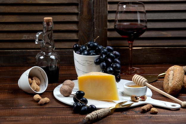 Tranche de parmesan servie avec du vin et du raisin