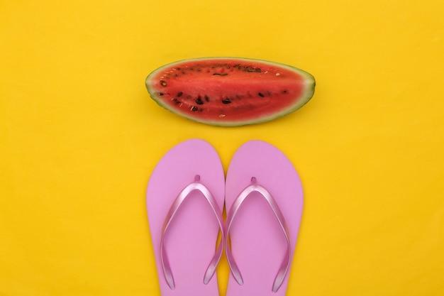 Tranche de pastèque mûre et tongs sur fond jaune. plaisirs d'été, repos sur la plage. vue de dessus. mise à plat