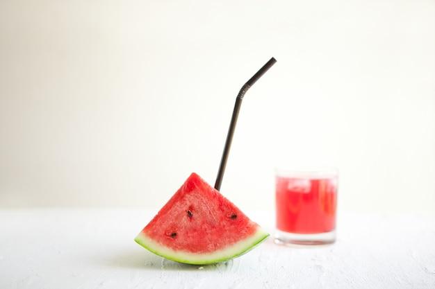 Tranche de pastèque avec de la paille et du jus sur le tableau blanc. délicieuse boisson - cocktail végétarien de fruits frais avec de la glace. image conceptuelle