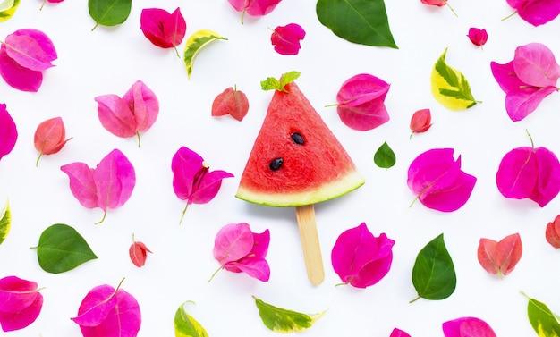 Tranche de pastèque popsicle avec une belle fleur de bougainvillier rouge et des feuilles sur fond blanc. concept de fond d'été