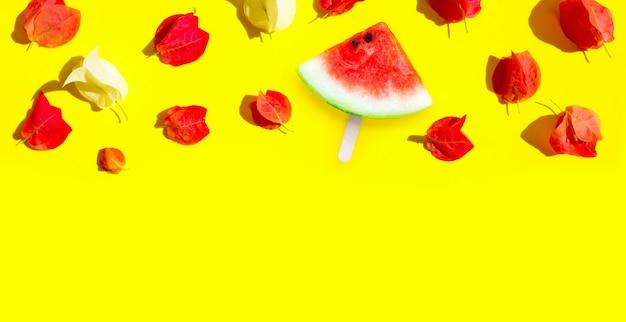 Tranche de pastèque popsicle avec des fleurs de bougainvilliers sur fond jaune.