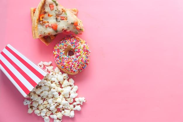 Tranche de pizza au fromage sur une assiette, beignets et pop-corn sur rose,