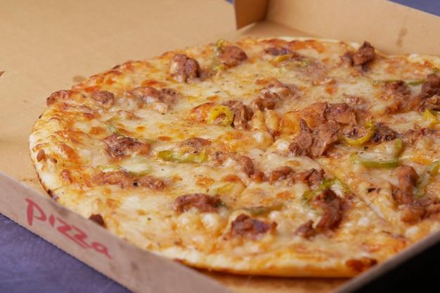 Tranche de pizza au fromage dans une boîte en papier sur la table