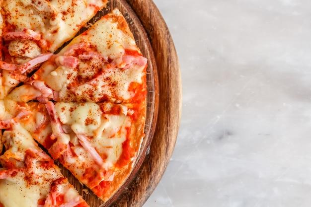 Tranche de pizza chaude avec du fromage fondant sur une table en pierre de granit blanc.