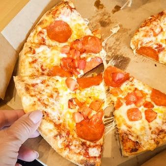 Une tranche de pizza à la main, vue de dessus.