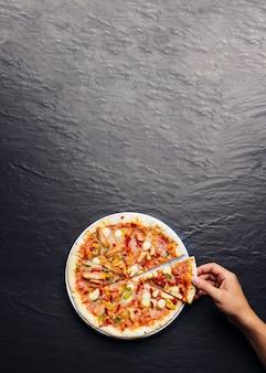 Tranche de pizza à la main