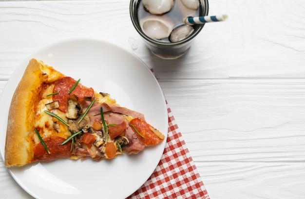 Tranche de pizza savoureuse au pepperoni, aux tomates, au fromage et au soda ice drink sur fond en bois blanc