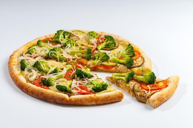 Tranche d'une pizza végétarienne séparée sur fond blanc, avec sauce tomate, brocoli, tomates, courgettes, aubergines et rondelles d'oignon