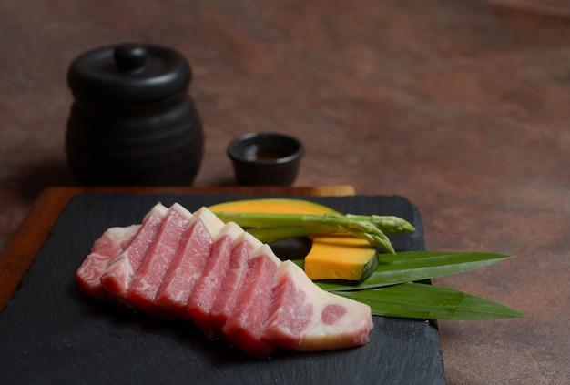 Tranche de poitrine de bœuf crue fraîche avec des morceaux de citrouille et des asperges sur le fond noir du plat, menu.