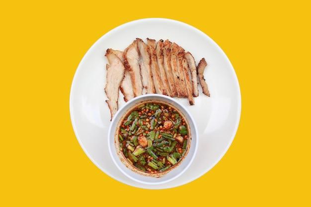 Tranche de porc grillé servi avec sauce épicée sur plaque blanche sur jaune