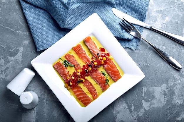 Tranche de saumon au poivre, sel de mer, herbes et huile d'olive. vue de dessus, espace pour le texte.