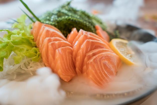 Une tranche de saumon cru ou un sashimi de saumon frais à la japonaise, servi sur glace dans un bol.
