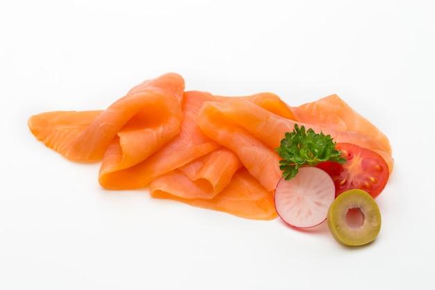 Tranche de saumon frais et épices sur fond blanc.