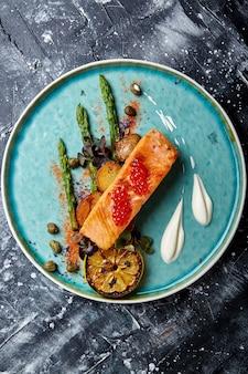 Tranche de saumon grillé garni d'asperges vertes cuites, de tomates cerises sautées et de citron