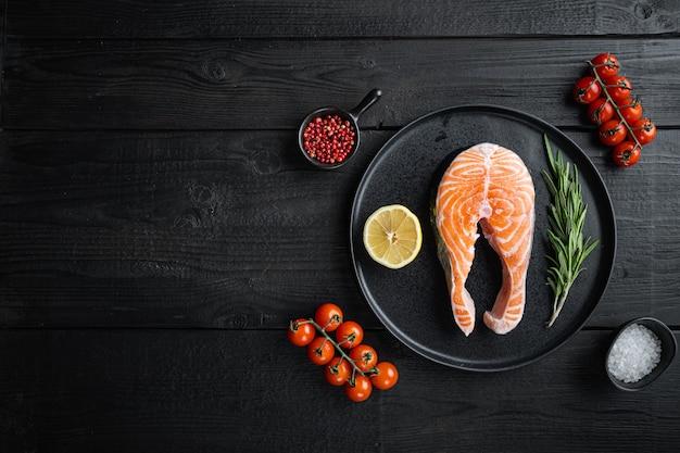 Tranche de saumon poisson rouge aux herbes, sur une surface en bois noire, vue à plat avec espace copie.