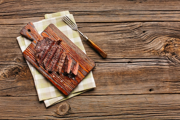 Tranche de steak grillé sur une planche à découper avec une fourchette et une serviette de table sur la table