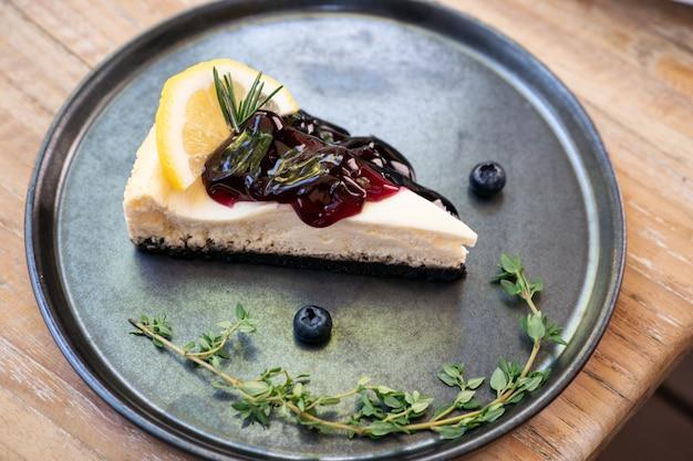Tranche de tarte au fromage aux bleuets sur plaque noire.