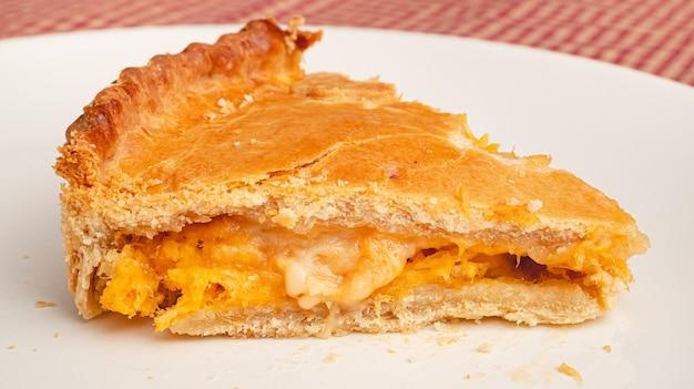 Une tranche d'une tarte au poulet caillé sur une plaque blanche de la cuisine brésilienne