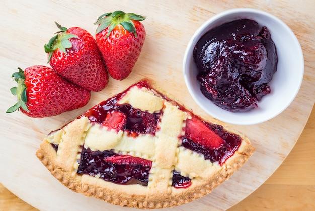 Tranche de tarte aux cerises maison et fraises sur table en bois