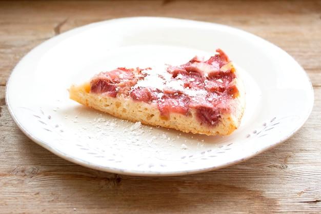 Tranche de tarte aux fraises sur plaque rose