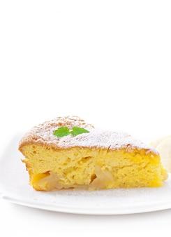 Tranche de tarte aux pommes sur une assiette décorée de feuilles de menthe