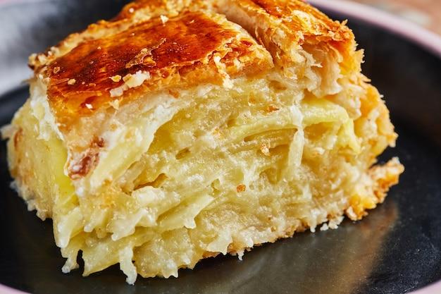 Tranche de tarte aux pommes de terre aux oignons, prêt après la cuisson sur plaque noire