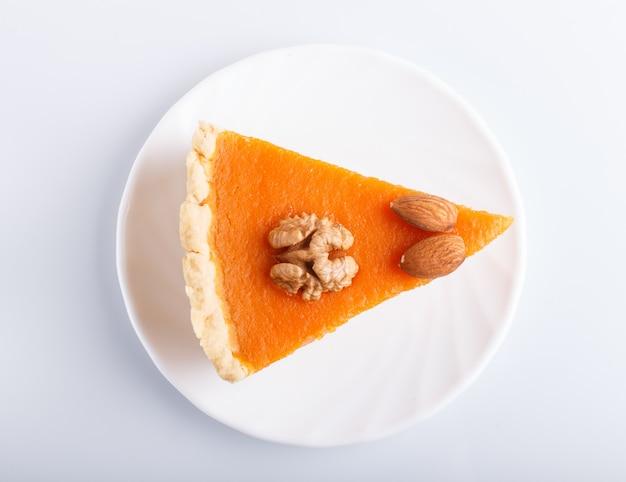 Une tranche de tarte à la citrouille douce américaine traditionnelle isolée sur une surface blanche.