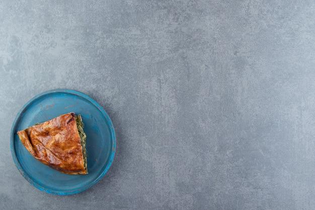 Tranche de tarte farcie aux verts sur une planche à découper noire.