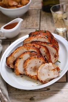 Tranché en tranches de poitrine de dinde cuite au four sous une sauce aigre-douce à la table du dîner