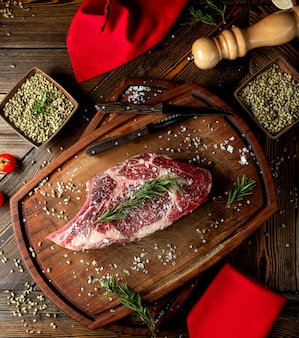 Tranche de viande crue garnie d'herbes et de sel