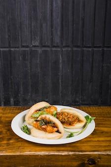 Tranche de viande cuite et autres condiments en sandwich entre du pain plat cuit à la vapeur sur une assiette