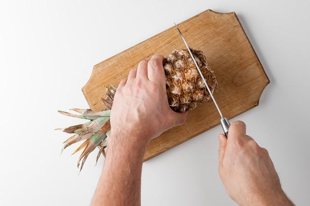Trancher des ananas avec un couteau sur un plateau de cuisine