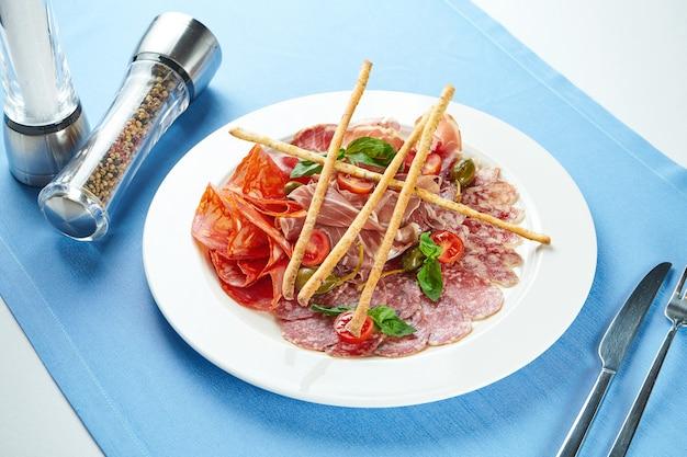 Trancher les chorizos italiens, le salami, le prosciutto di parma. antipasti dans une assiette blanche sur une nappe bleue