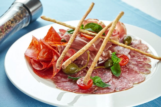 Trancher les chorizos italiens, le salami, le prosciutto di parma. antipasti dans une assiette blanche sur nappe bleue