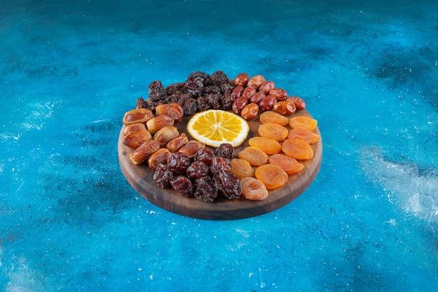 Trancher le citron et les fruits secs sur une planche, sur la table bleue.