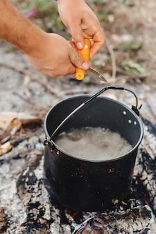 Trancher les légumes pour le bouillon de poisson dans la nature près du feu