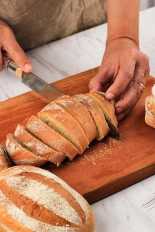 Trancher à la main le pain de foyer au lait japonais à l'aide d'un couteau à pain pour le petit-déjeuner. le pain de foyer au lait est un pain japonais au lait ou à la crème fouettée, doux et moelleux. focus sélectionné