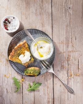 Trancher la quiche dans une assiette avec la roquette, l'oignon, les épinards, la mozzarella, la feta et la sauce à la rustique, vue de dessus.
