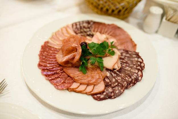 Trancher la viande et les saucisses.