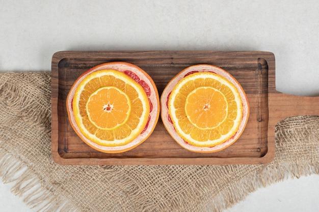 Tranches d'agrumes frais sur planche de bois