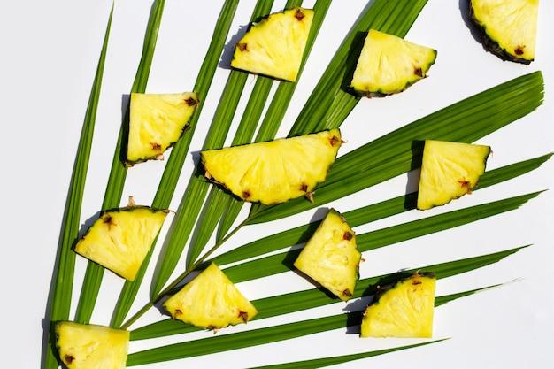 Tranches d'ananas frais sur des feuilles de palmier tropical sur une surface blanche