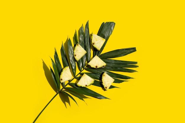 Tranches d'ananas frais avec des feuilles vertes sur une surface jaune