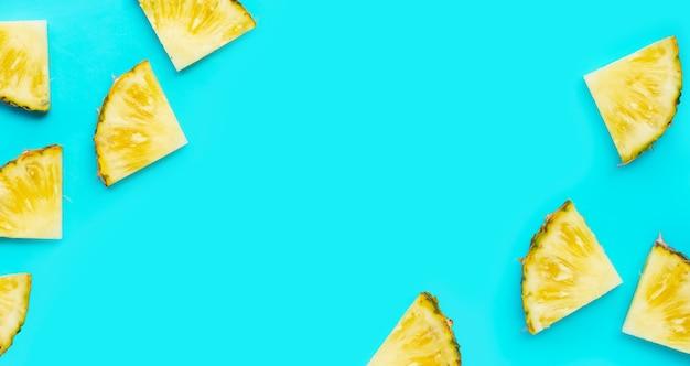 Tranches d'ananas frais sur fond bleu.