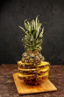 Tranches d'ananas moelleux mûrs juteux magnifiquement conçus sur un bureau brun et un plancher en bois
