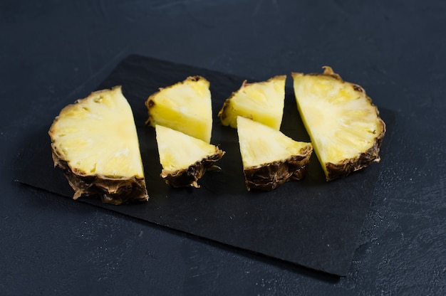 Tranches d'ananas sur un tableau de pierre noire avec un espace pour le texte
