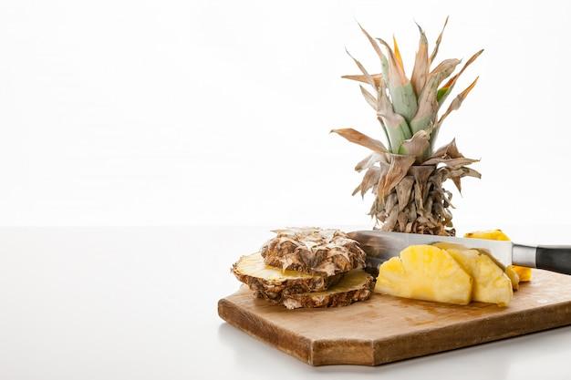 Tranches d'ananas tranchées au couteau sur un plateau de cuisine