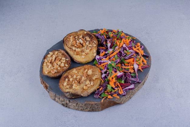 Tranches d'aubergines frites garnies d'ail et une portion de salade sur fond de marbre.